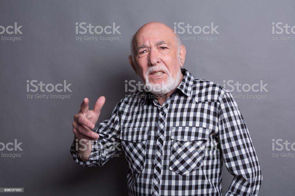 Furious senior man shouting, point at camera stock photo