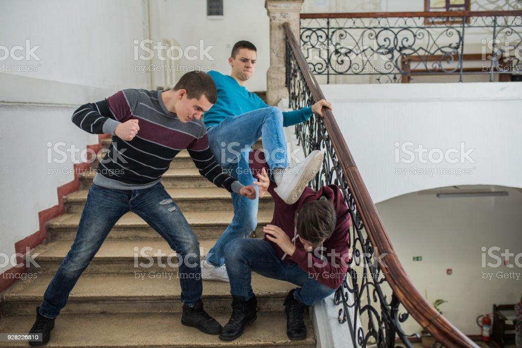 Furious teenage boys bullying their classmate in a high school hallway. stock photo