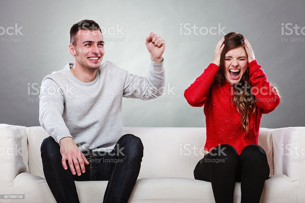 Furious wife and happy husband. Disagreement stock photo