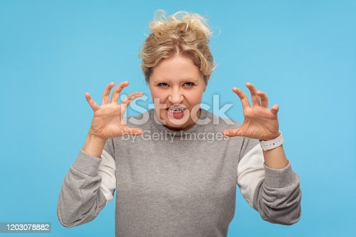 808681534 istock photo Furious woman with curly hair in sweatshirt standing with raised claws and clenched teeth, experiencing strong anger, irritation 1203078882