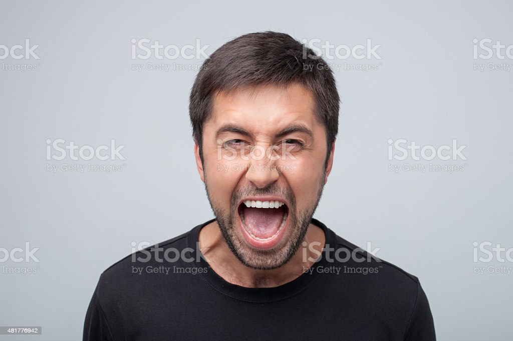 Furious young man is evincing negative emotions stock photo