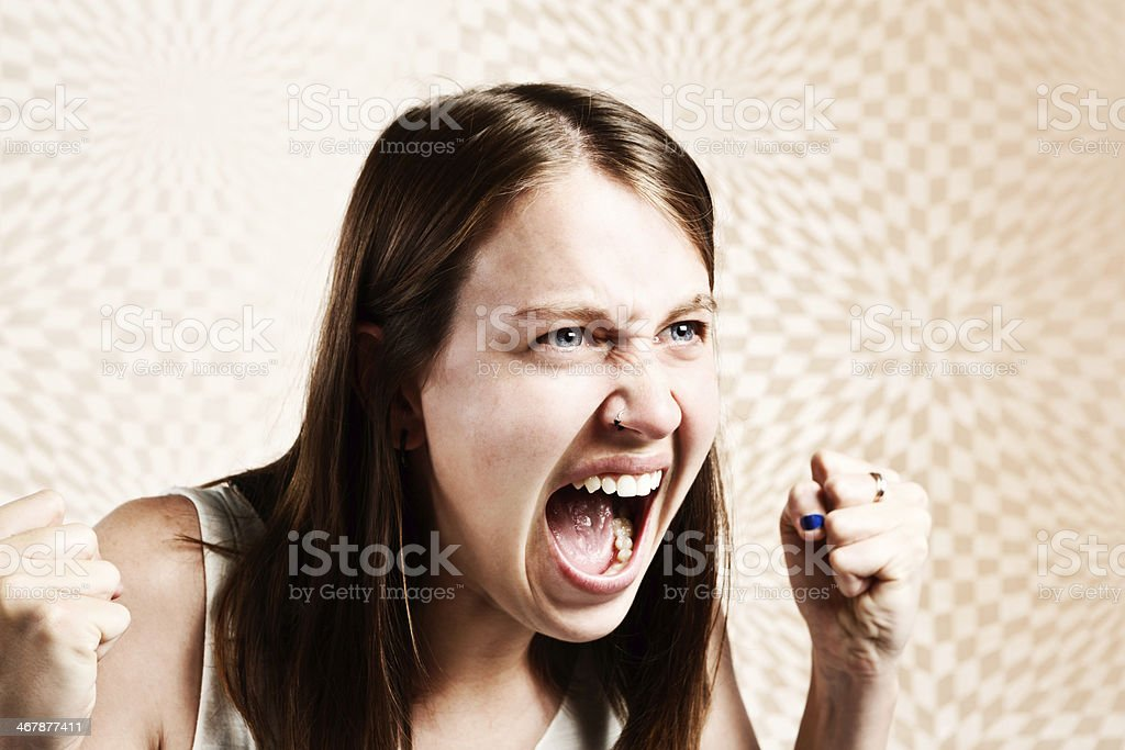 Furious young woman with clenched fists yells in defiant rage royalty-free stock photo