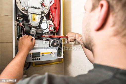 Repairman servicing or repairing furnace