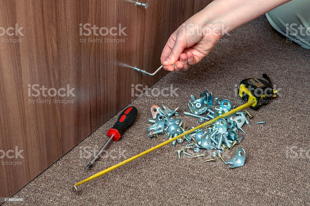 Furniture assembly hand tool, hex wrench screw screwed into furniture. stock photo