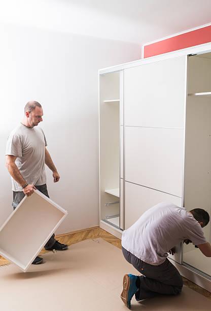 furniture maker sets wardrobe - telefonschrank stock-fotos und bilder