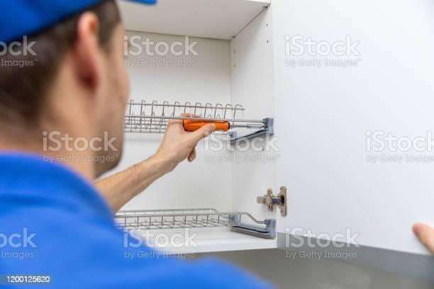 Furniture service worker screwing kitchen cabinet dish rack picture id1200125620?b=1&k=6&m=1200125620&s=612x612&h=uwkzpl9x4vjjpbivujatwgpfjjtdnp20qsyrhdogndk=
