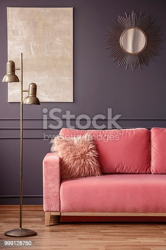 Furry pillow on a powder pink sofa, elegant golden sunburst mirror and marble painting on a dark gray wall in a living room interior