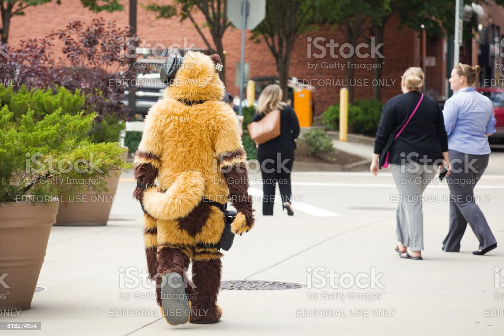 A furry in town for Anthrocon 2017 walks among the working crowd on...