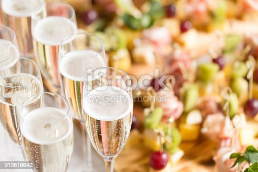 istock Furshet. Table top full of glasses of sparkling white wine with canapes and antipasti in the background. champagne bubbles 913616642