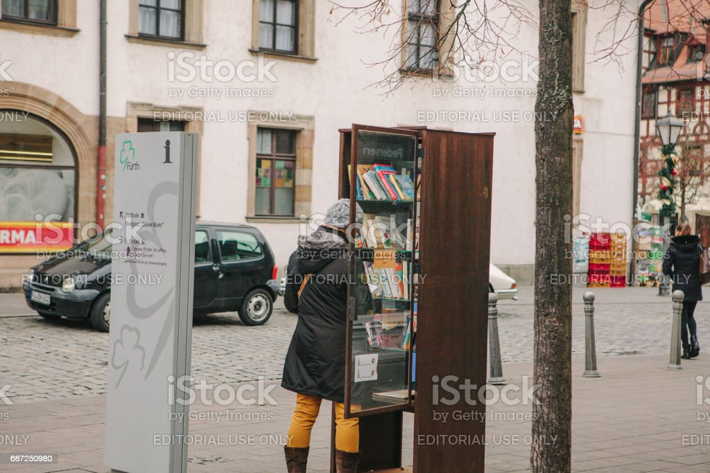 Furth, Germany, December 28, 2016: A woman chooses a book. Street public library. Education in Germany. Lifestyle. Everyday life in Europe. Bookshelves. stock photo