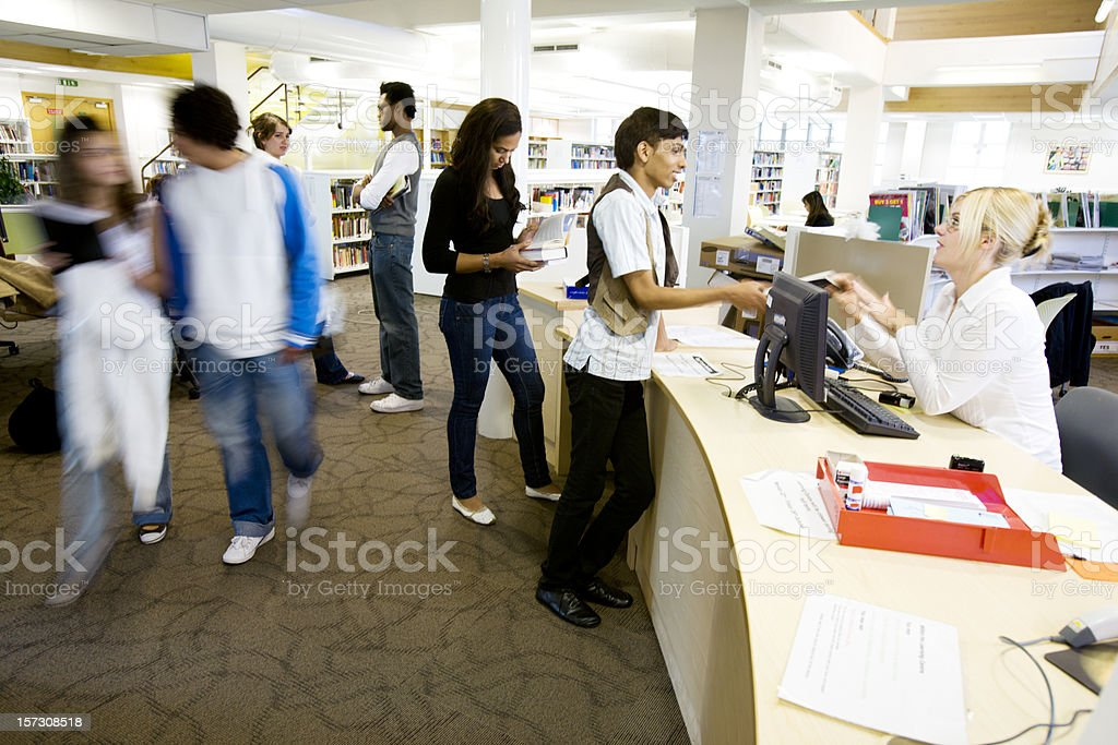 further education: candid college library scene with librarian helping pupils royalty-free stock photo
