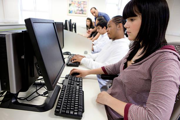 nastoletnie studentów: koncentracja na twarzy uczniów za pomocą komputera - człowiek maszyna zdjęcia i obrazy z banku zdjęć