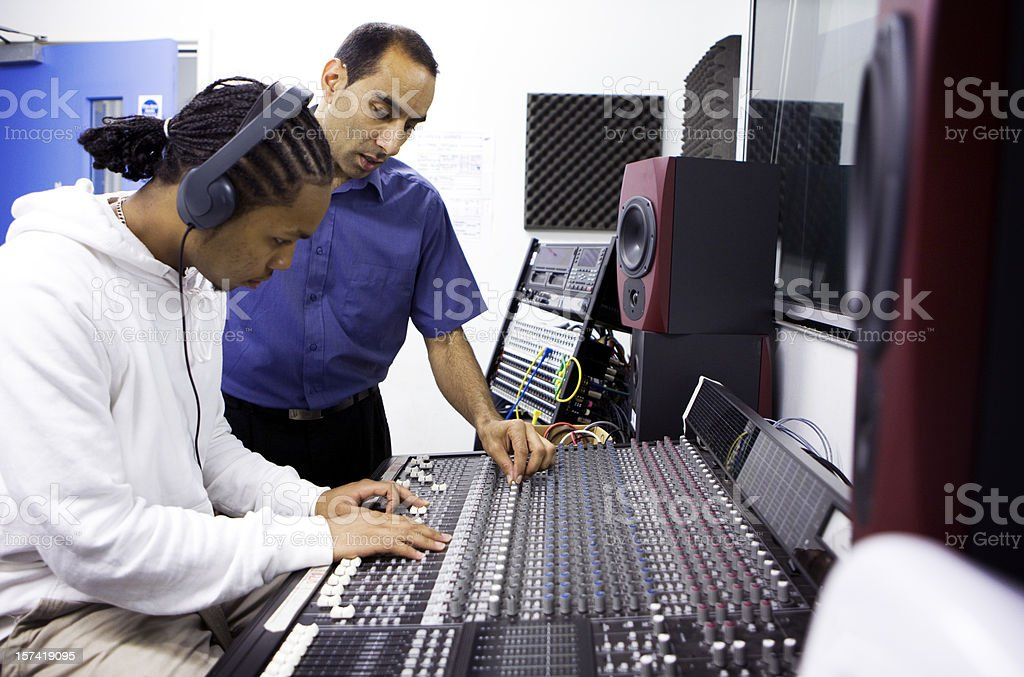 further education: teacher and pupil on recording studio mixing desk royalty-free stock photo