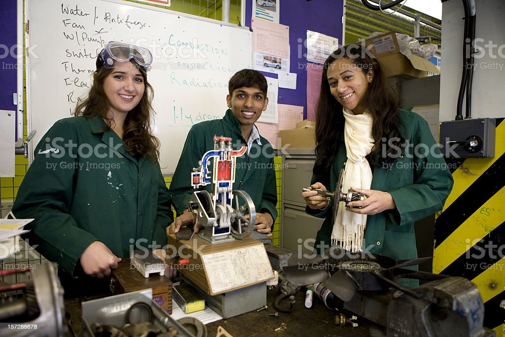 further education: trainee mechanics smiling as they learn their trade royalty-free stock photo