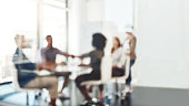 Defocused shot of businesspeople shaking hands during a meeting in an office