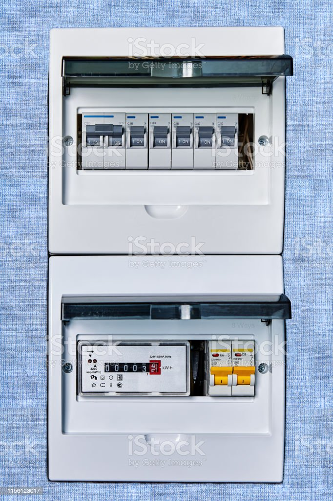 Fuse box controls electricity in home. Electric circuit breaker box of home electrical system with new modern electronic electrical meter. Apartment Stock Photo