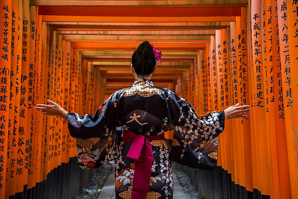 Fushimi Inari shrine in Kyoto, Japan Kyoto, Japan - October 8, 2016: Unidentified woman at walkway in Fushimi Inari shrine in Kyoto, Japan. This popular shrine have 32,000 sub-shrines  throughout Japan shinto shrine stock pictures, royalty-free photos & images