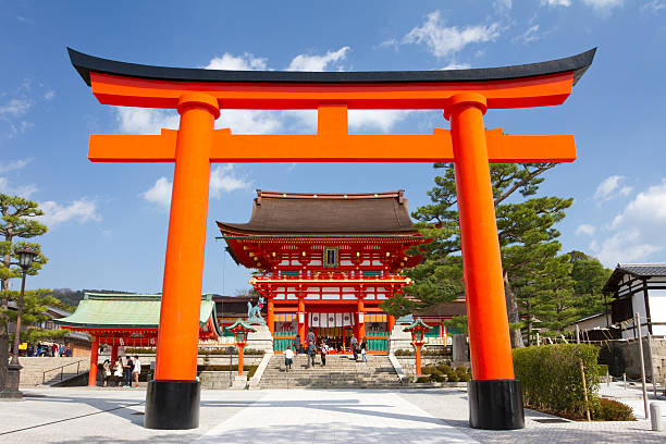 Fushimi Inari Shrine, Kyoto, Japan Kyoto, Japan - March 19, 2013: A giant torii gate in front of the Romon Gate at Fushimi Inari Shrine's entrance. Fushimi Inari Shrine is the head shrine of Inari, located in Fushimi-ku, Kyoto, Japan. It is famous for its thousands of vermilion torii gates, which straddle a network of trails behind its main buildings. shinto stock pictures, royalty-free photos & images