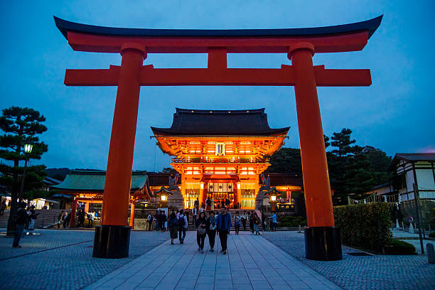 Fushimi Inari Shrine Kyoto, Japan - October 22, 2016: Tourists beneath a huge torii gate at the entrance to the Fushimi Inari Shrine. shinto shrine stock pictures, royalty-free photos & images
