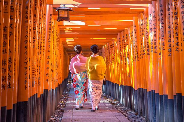 Fushimi Iniari Shrine in Kyoto, Japan Kyoto, Japan - December 13, 2014: Two geishas walking through orange gates called torii at the Fushimi Inari Shrine geisha stock pictures, royalty-free photos & images