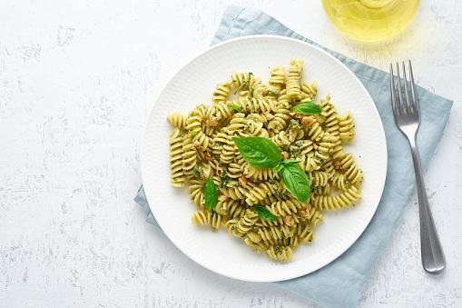 fusili pasta with basil pesto and herbs, italian cuisine, gray stone background, top view