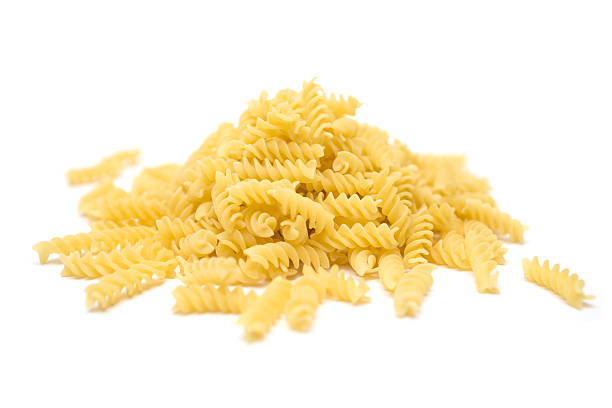 Fusilli Heap of raw Italian pasta isolated on a white background. fusilli stock pictures, royalty-free photos & images