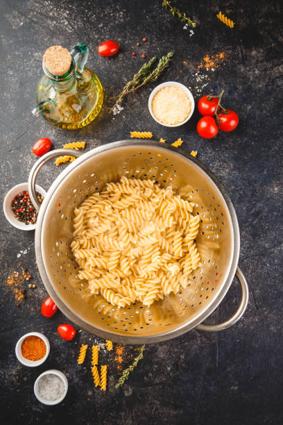 Fusilli pasta in a stainless steel colander Fusilli pasta in stainless steel colander and ingredients over dark background. Top view or flat-lay. fusilli stock pictures, royalty-free photos & images