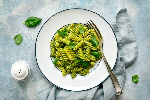 Fusilli pasta with basil pesto Fusilli pasta with basil pesto on a plate over light blue slate, stone or concrete background. Top view with copy space. fusilli stock pictures, royalty-free photos & images