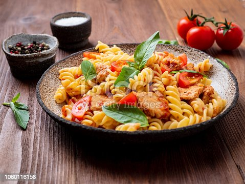 fusilli pasta with tomato sauce, chicken fillet with basil leaves on dark brown wooden background, side view