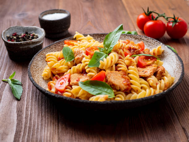fusilli pasta with tomato sauce, chicken fillet with basil leaves on dark brown wooden background, side view fusilli pasta with tomato sauce, chicken fillet with basil leaves on dark brown wooden background, side view fusilli stock pictures, royalty-free photos & images