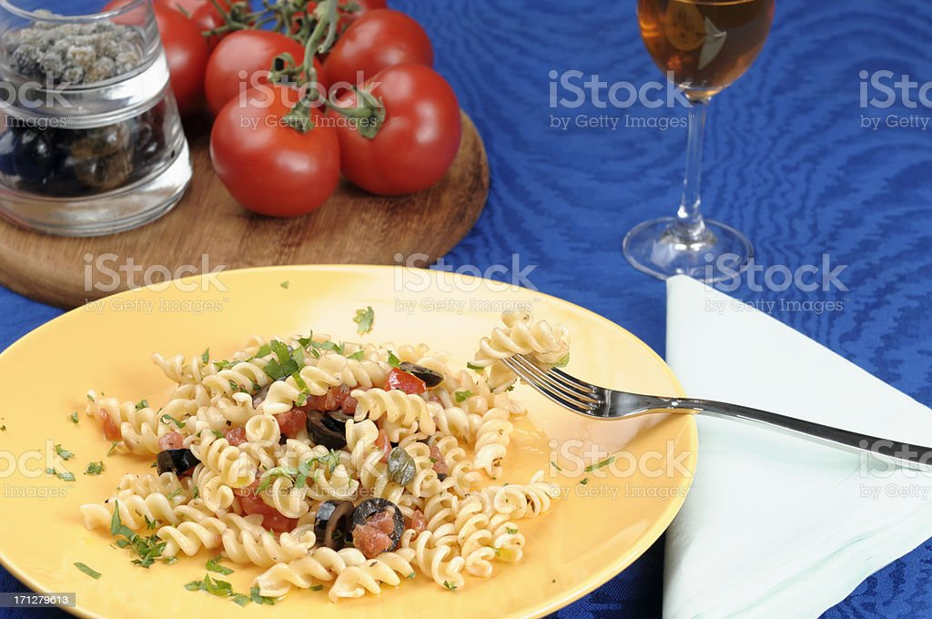 Fusilli pasta with tomatoes, black olives, capers royalty-free stock photo