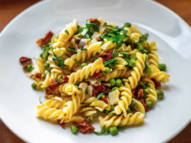 Fusilli pasta with vegetable on plate. Fusilli pasta with dried tomato, peas, rucola leaf and cheese parmesan pieces on white plate, closeup. fusilli stock pictures, royalty-free photos & images