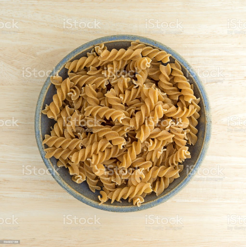 Fusilli whole wheat organic pasta in an old bowl stock photo