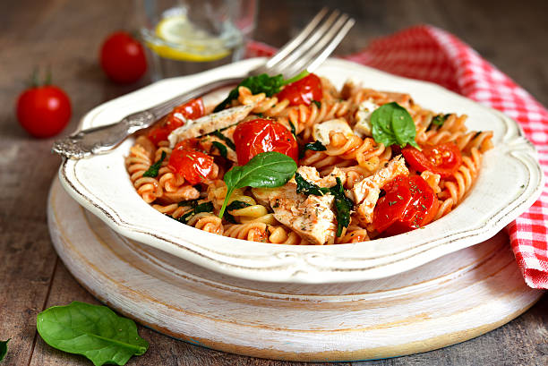 Fusilli with chicken,spinach and cherry tomatoes. Fusilli with chicken?spinach and cherry tomatoes in tomato sauce. fusilli stock pictures, royalty-free photos & images