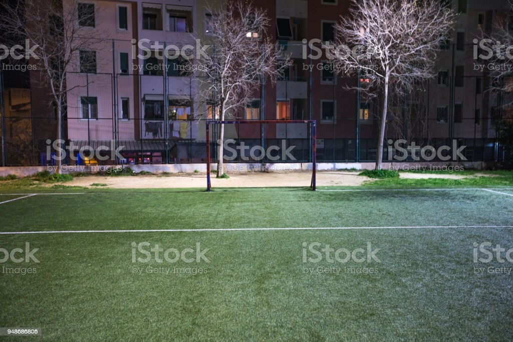 Futsal, small soccer or football field in a park at night with lights