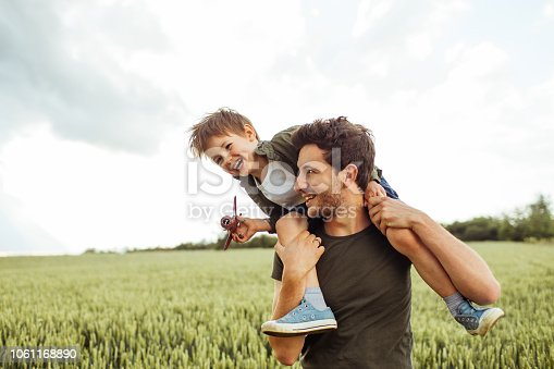 Photo of a cheerful little boy, being supported to be a pilot, by his father who is holding him on shoulders