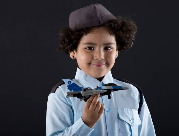 Future airwoman holding toy fighter plane Little Indian girl in air force costume holding toy fighter jet flight suit stock pictures, royalty-free photos & images