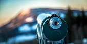 Close up of tourist binocular in Austria, wintertime, sundown with sunbeams