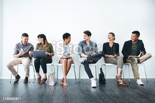 Studio shot of a group of businesspeople chatting in a waiting room