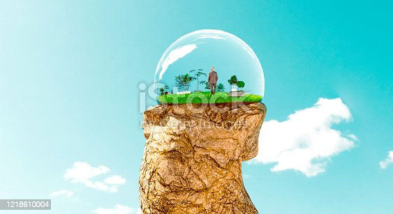 Concept of future living. House made of glass on top of rock. The house is full of plants and flowers.