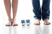 Future mom and dad feet with little baby shoes on the floor. Happy young family awaiting baby, love and happiness, new life concept
