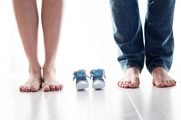 Futura mamá y Papá cuadrados con poco de zapatos de bebé - foto de stock