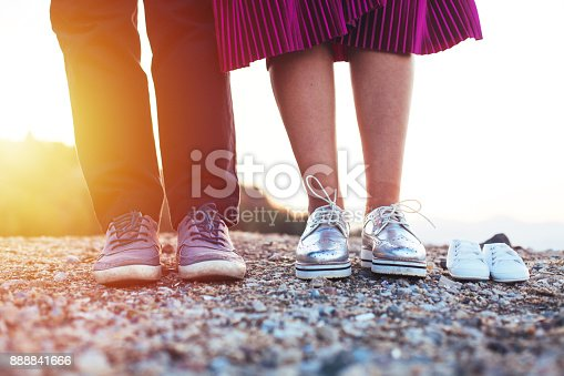 Future mom and dad feet with little baby shoes