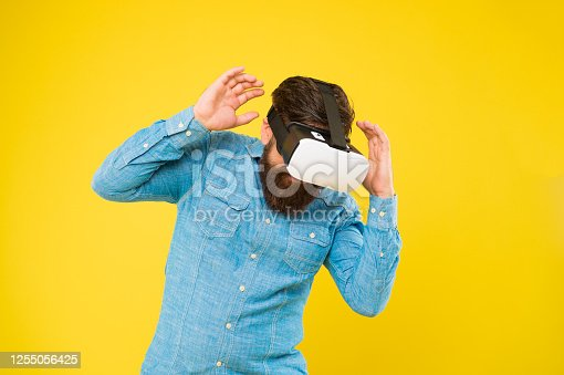 istock Future of entertainment and communication. Hipster wear VR glasses. Future vision. Bearded man explore VR yellow background. Virtual reality technology and future. Stepping into future 1255056425