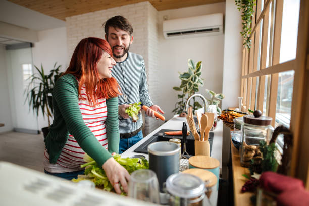 Future parents having fun in the kitchen while preparing a salad for lunch stock photo