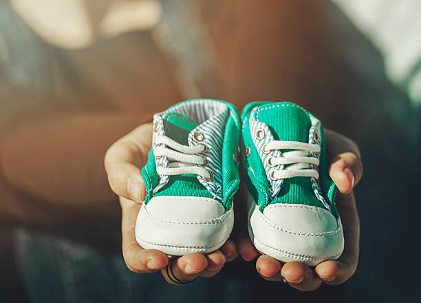 Futur parents tenant une paire de petites chaussures - Photo