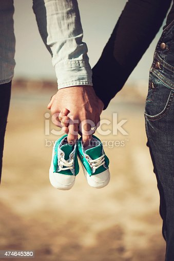 Future parents holding hands and a pair of little shoes