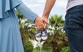 Future parents holding hands and baby shoes while walking outdoors