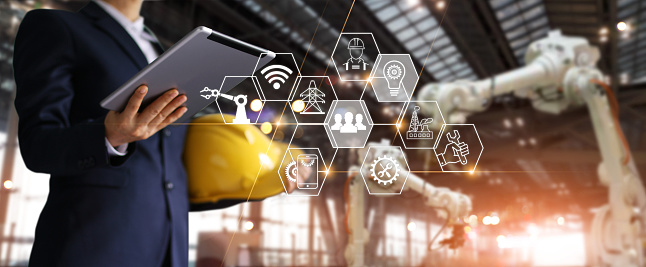 istock A futuristic architect, Businessman, Engineer manager using tablet with icon network, Industrial robotics, Automation robot arms machine in intelligent construction site. Construction technology concept 1022854988