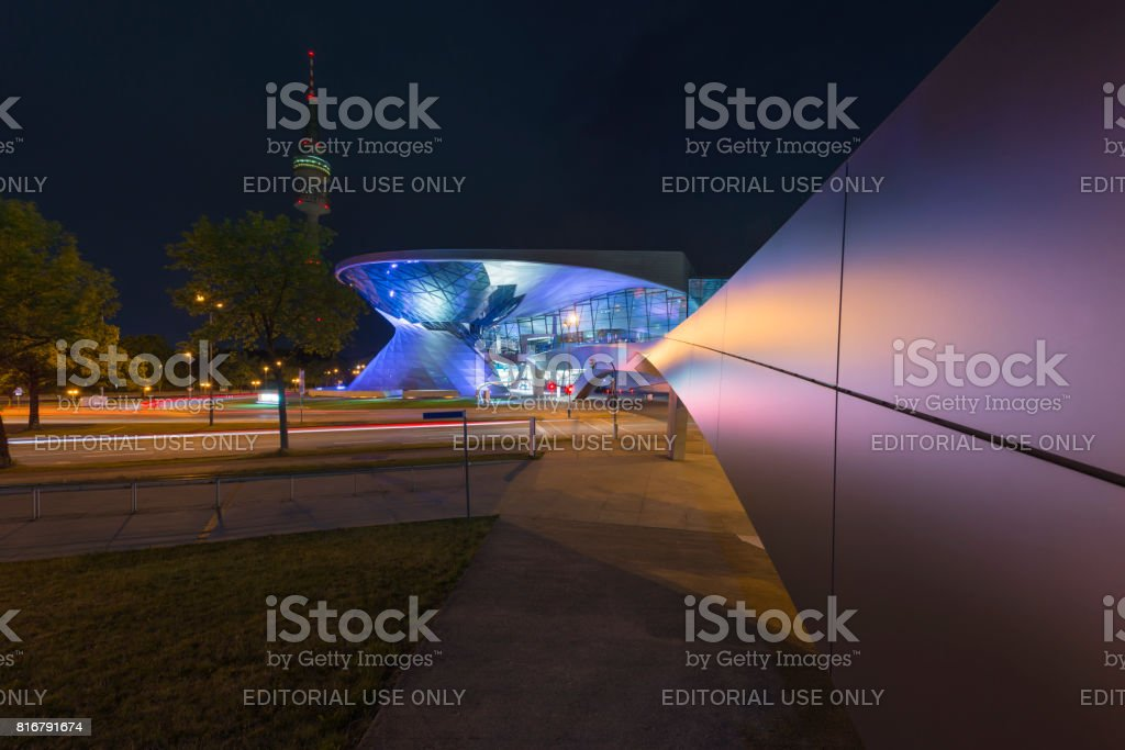 Futuristic architecture of a walkway towards the illuminated facade of the BMW Welt in Munich at night stock photo